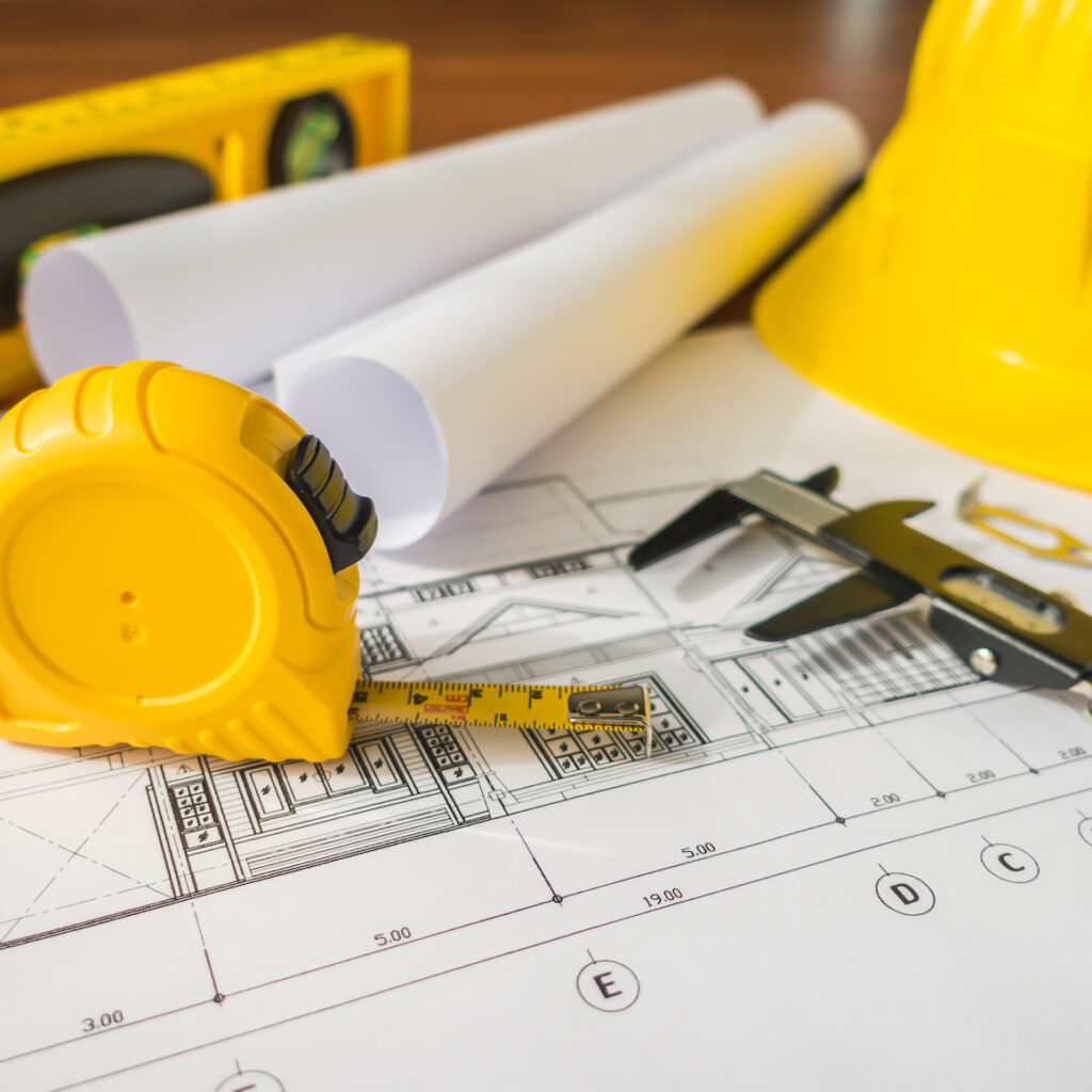 Construction plans with yellow helmet and drawing tools on blueprints.